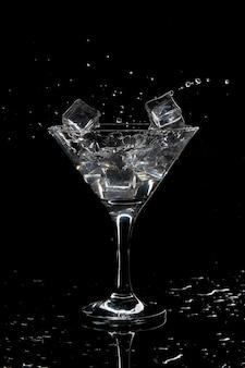 Splash van cocktail martini met ijs op een zwarte achtergrond