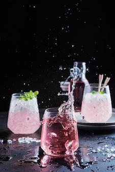 Splash van een roze cocktail op de zwarte achtergrond