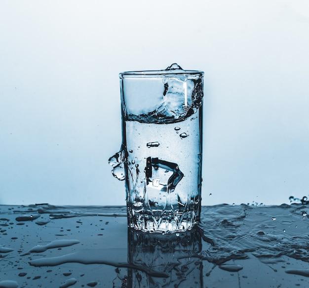 Splash van ijsblokje in een glas water, op de natuurblauw
