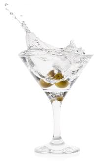 Splash van martini met olijven in cocktail transparant glas op t