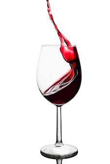 Splash van rode wijn in een glas op wit