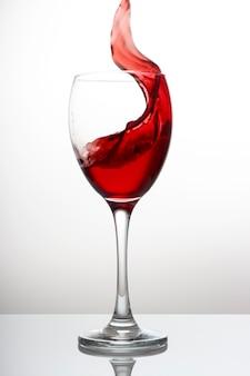 Splash van rode wijn in een kristalglas