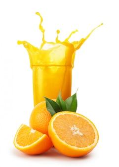 Splash van sinaasappelsap en sinaasappelen met groene bladeren