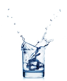 Splash van water in een breed glas met ijs