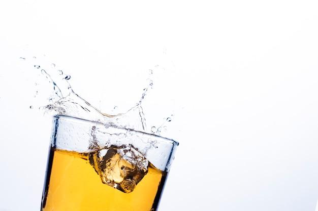 Splash whisky van ijsblokjes. concept alcoholische dranken met ijs, whisky of brandewijn, appelsap en koeldranken.