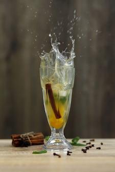 Splashkop hete vitaminethee op houten lijst. winter warme seizoensgebonden drankjes