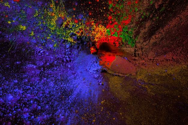 Splatter van holi kleurpoeder over zwart oppervlak
