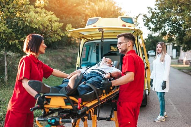 Spoedeisende medische dienst op het werk. paramedicus trekt brancard met senior man met ernstige hartaanval naar de ambulance auto. hulp op de weg. bestuurdersassistentieconcept.