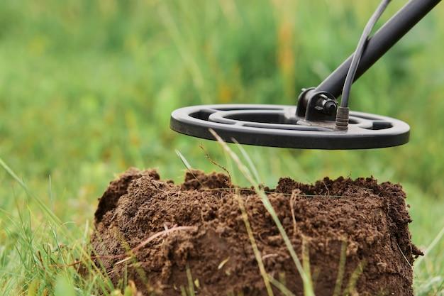 Spoel van metaaldetector op achtergrond van grond en gras op weide