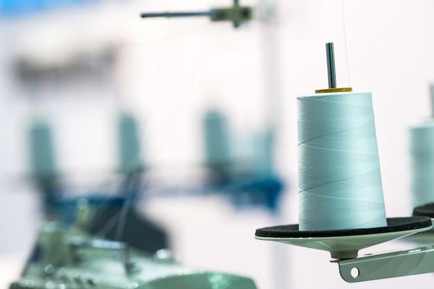 Spoel van witte draden op naaimachine, close-up