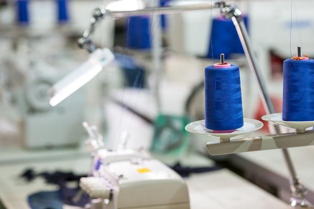 Spoelen van blauwe draden op naaimachine, fabriek