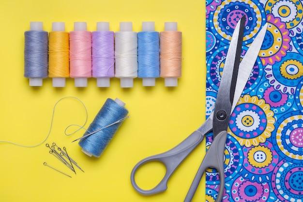 Spoelen van gekleurde draden. naald om te naaien, schaar.
