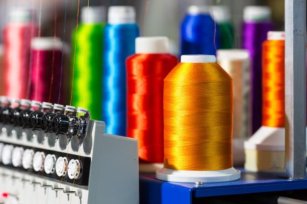 Spoelen van kleur draden close-up, draaiende machine. lakenfabriek, weverij, textielproductie, kledingindustrie, naaistof