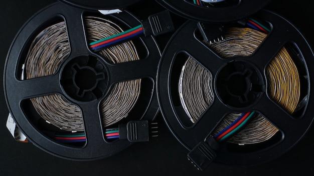 Spoelen van rgb ledstrip op een zwarte tafel. ledstrip voor creatieve verlichting verzameld in een zwarte spoel, gereedschap voor verlichting en lichteffecten.
