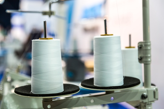 Spoelen van witte draden op naaimachine, close-up
