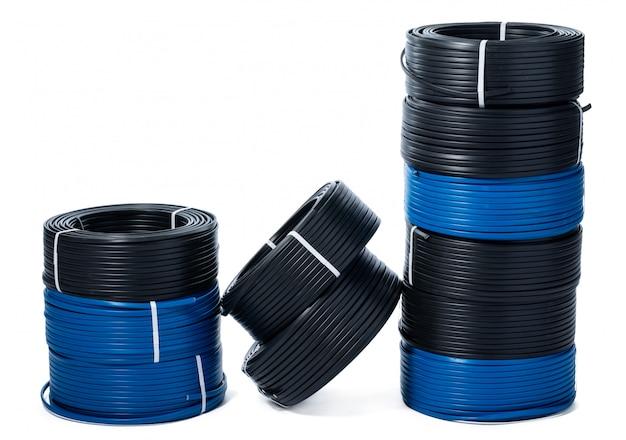 Spoelen van zwarte en blauwe kabel die op witte oppervlakte wordt geïsoleerd