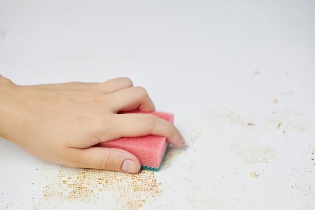 Spons in vrouwenhand verwijdert vuil, broodkruimels en restjes. schoonmaak keukentafel. huishoudelijke taken