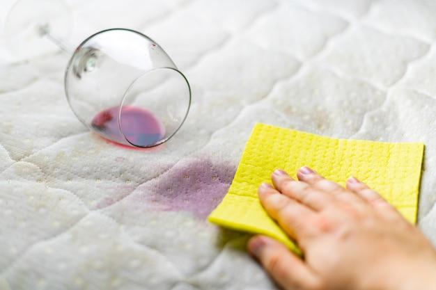 Spons schoonmaak wijn vlek. wijnglas laten vallen. gemorste wijn op witte bank.