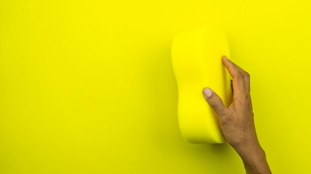 Spons van de hand de mannelijke holding op gele kleur.