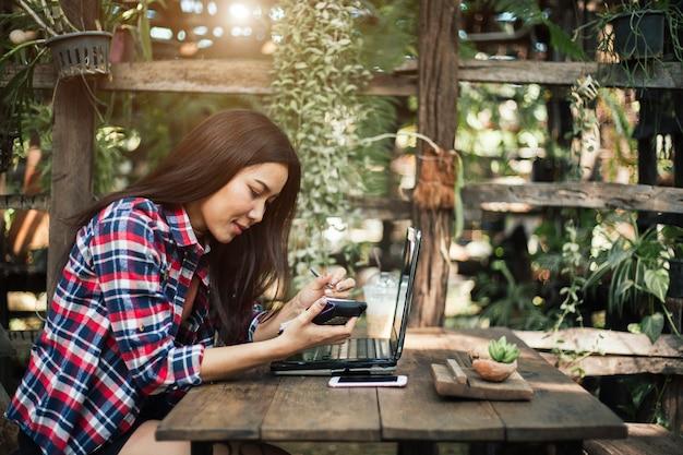 Spontaan beeld van een jonge vrouw die tabletcomputer in een koffie met behulp van
