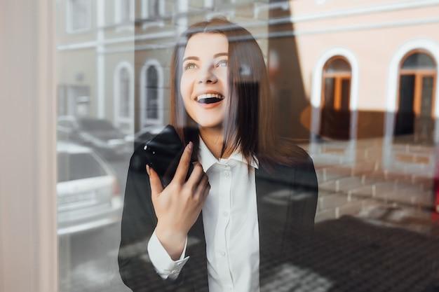Spontaan beeld van een onderneemster die op de telefoon in een koffie spreekt.