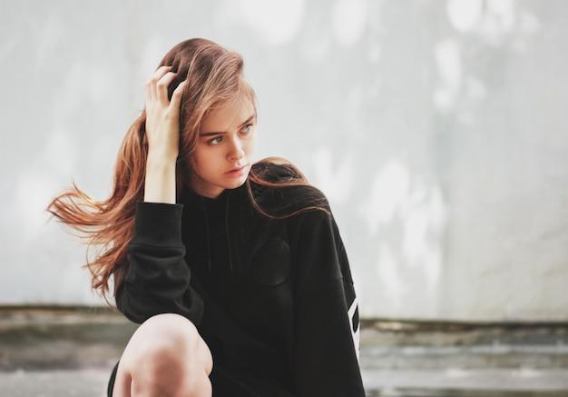 Spontaan portret van de jonge mooie lange mannequin van het haarmeisje hipster in zwarte hoodie