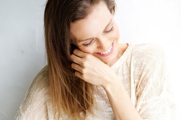 Spontaan portret van een vrouw die tegen witte achtergrond lacht