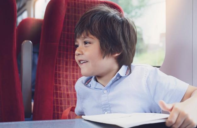 Spontaan schot opgewonden kind kijkt uit de trein met blij gezicht, schooljongen plezier maken reizen met de trein voor een dagtocht, schattige kleine jongen met lachende gezicht gelukkige tijd op zijn zomerkamp.
