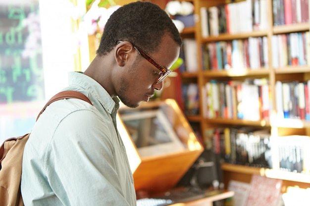Spontaan schot van geconcentreerde zwarte europese mannelijke student met rugzak die aan onderzoek naar universiteitsbibliotheek werkt. stijlvolle donkere man op zoek naar zinnenboek in boekhandel voor vakanties in het buitenland