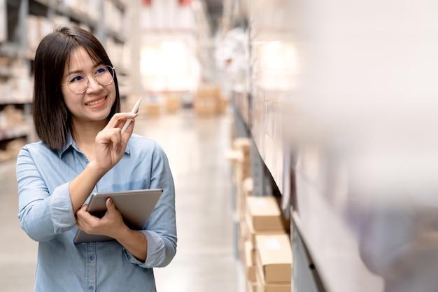 Spontane aantrekkelijke aziatische werknemer of personeel dat in opslaginventaris werkt