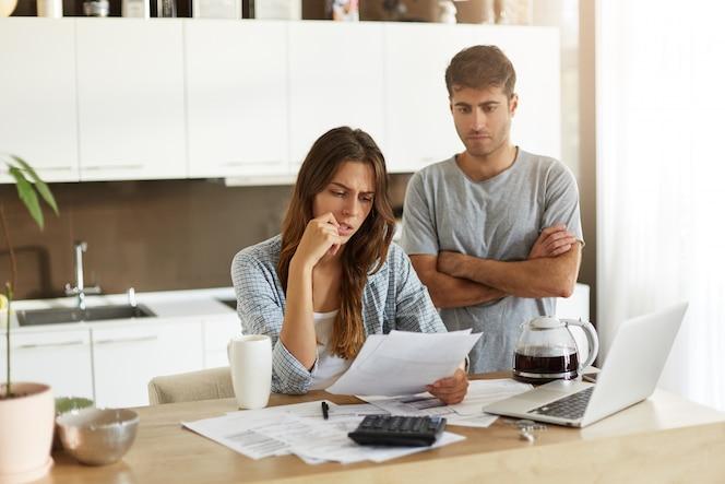 Spontane opname van jonge amerikaanse man en vrouw gekleed terloops gevoel gestrest terwijl ze samen de financiën in de keuken beheren, uitgaven berekenen, online rekeningen betalen voor de laptop