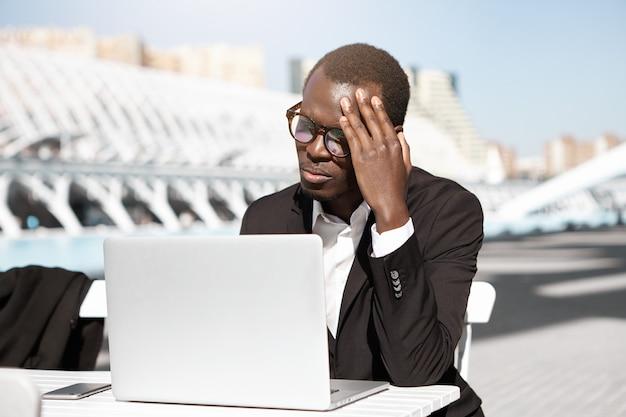 Spontane opname van ongelukkige jonge afro-amerikaanse manager die zich moe en gefrustreerd voelt, zittend in een stedelijk café met generieke laptop pc, hoofd aanraakt, probeert zich te concentreren op werk, uitgeput kijkt