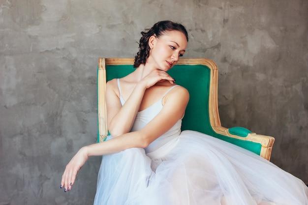 Spontane portret van ballet danseres ballerina in mooie licht blauwe jurk tutu rok poseren zittend op vinage stoel in loft studio