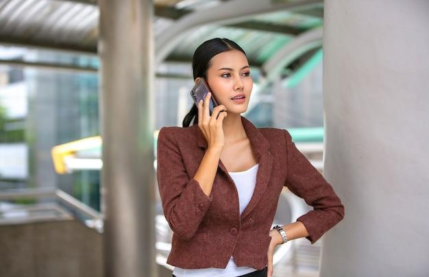 Spontane portretten van bedrijfsvrouwen die mobiele telefoon met behulp van openlucht