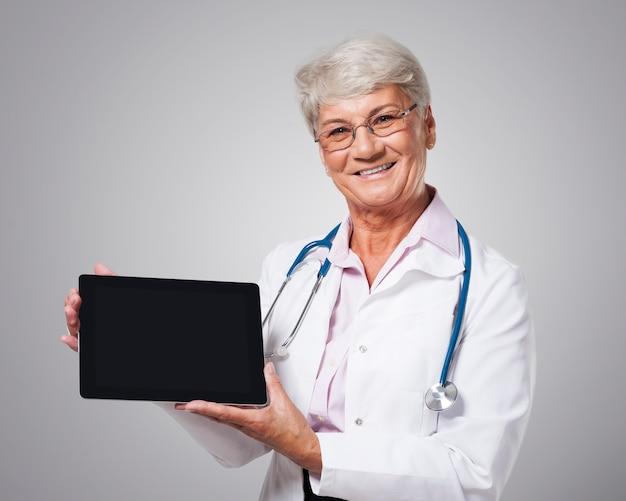 Spontane vrouwelijke arts die scherm van digitale tablet toont