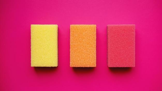 Sponzen - bovenaanzicht. huishoudelijk schoonmaakconcept. kleurrijke oranje roze gele sponzen op roze achtergrond.