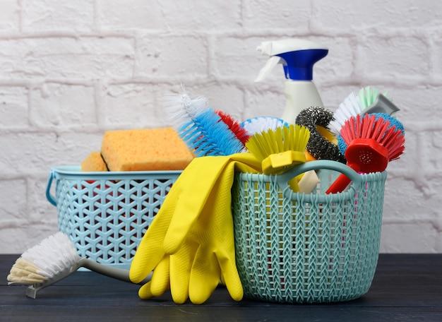 Sponzen, plastic borstels en flessen wasmiddelen op een blauwe houten tafel. huishoudelijke schoonmaakartikelen op een witte bakstenen muur