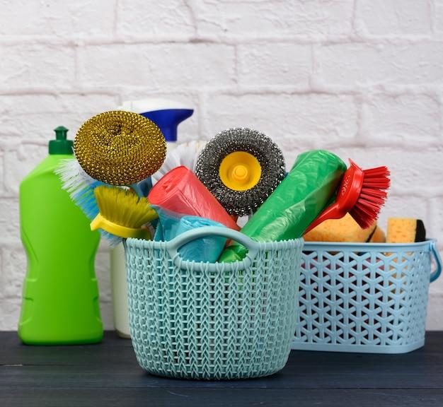 Sponzen, plastic borstels en flessen wasmiddelen op een blauwe houten tafel. huishoudelijke schoonmaakartikelen op witte bakstenen muurachtergrond