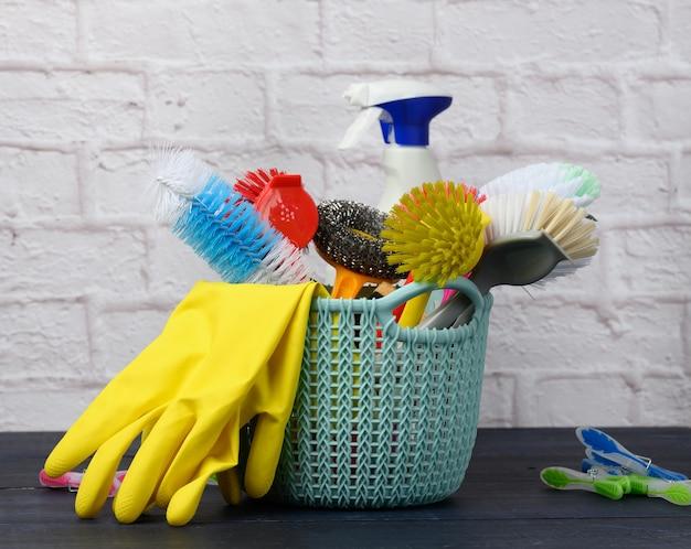 Sponzen, plastic borstels en flessen wasmiddelen op een blauwe houten tafel