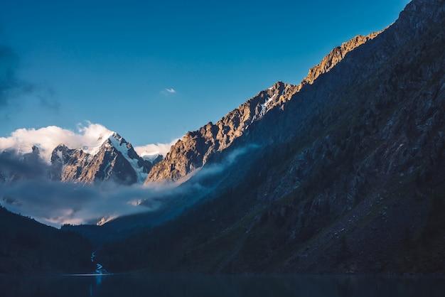 Spookachtig bos dichtbij bergmeer in vroege ochtend. de bergkreek van gletsjer stroomt in meer. mist op het wateroppervlak. lage wolk tussen rots. donker sfeervol mistig houtlandschap. rustige sfeer