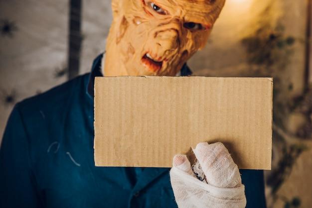 Spookachtige man die kleine tablet toont