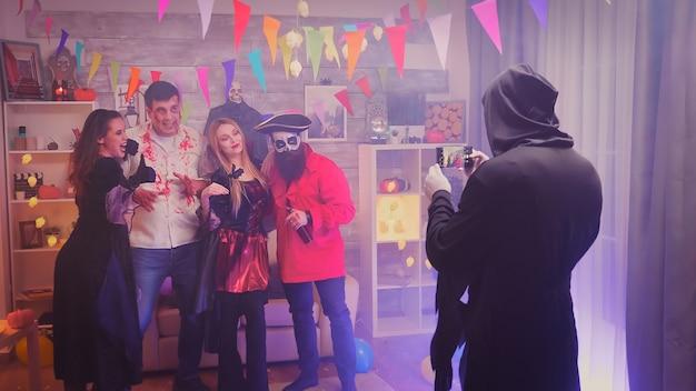 Spookachtige personages die een groepsfoto maken op een halloweenfeest in een ingerichte kamer.