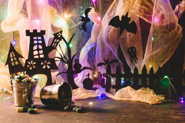Spookhuis met een graf en een enge boom op een houten muur met een spinneweb en led-slinger