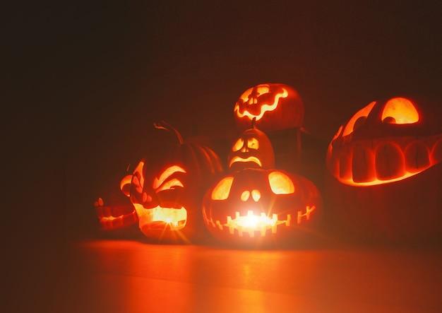 Spookpompoenen op halloween. e jack op donkere achtergrond. vakantie indoor decoraties.