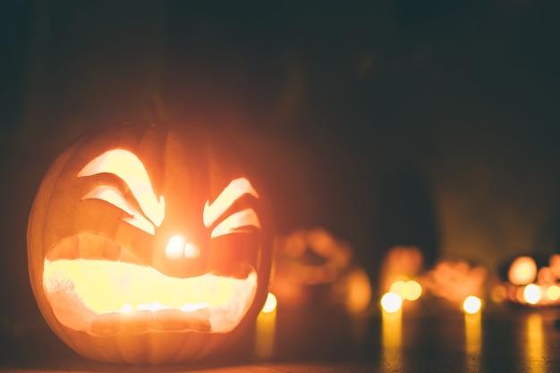 Spookpompoenen op halloween. ead jack op donkere achtergrond. vakantie indoor decoraties.