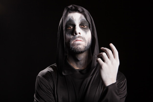 Spooky man verkleed als een magere hein op zwarte achtergrond. halloween-mysterie.