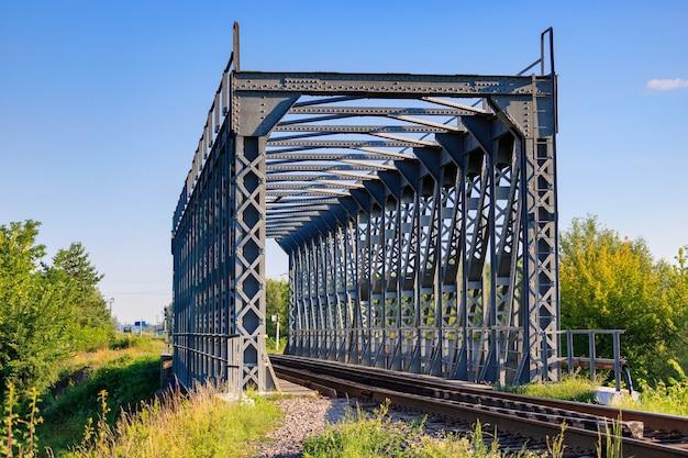 Spoorbrug in platteland tegen blauwe hemel en bomen
