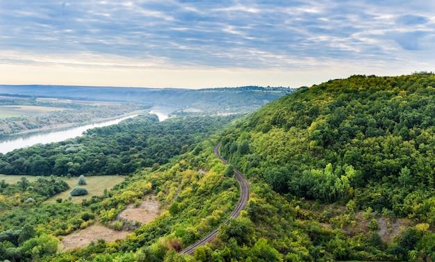 Spoorlijn gaat door de rotsen bij de rivier de dnjestr.