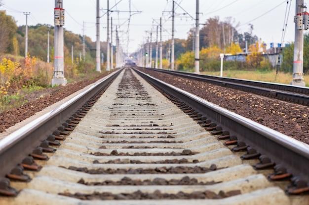 Spoorlijn met hoogspanningsmasten in perspectief gaan de horizon in