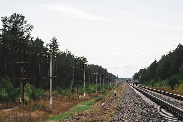 Spoorwagon gaat door rails in het bos. palen met draden langs rails. sfeervol vintage spoorweglandschap.